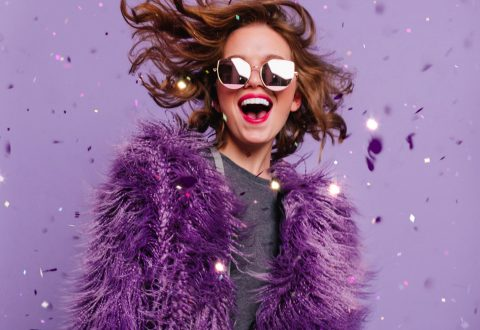 Young woman in purple faux fur jacket celebrates